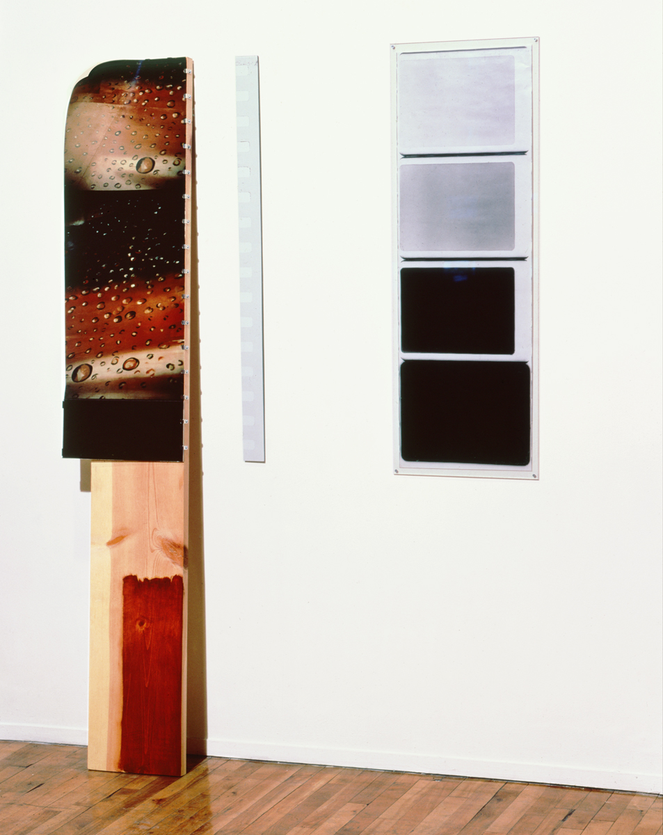 Jennifer Bolande, Flagship Episode, 1985, b/w photos, masonite, C print, clipped onto stained wooden board, plexi, brackets, 69h x 48w x 8d in.